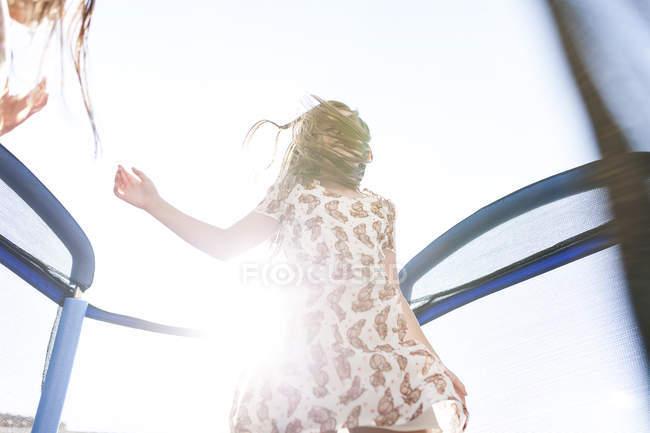 Девочки носить летнее платье, прыжки на батуте — стоковое фото