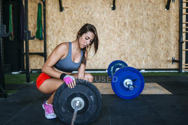 Kaukasische sportliche Frau Vorbereitung Langhantel im Fitness-Studio — Stockfoto
