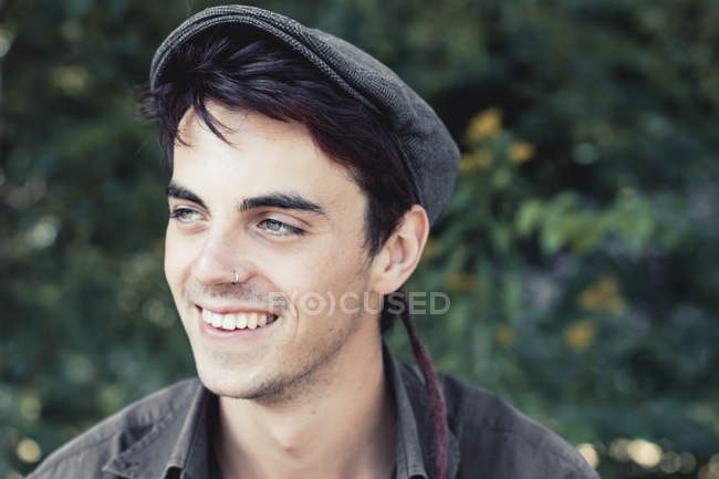 Portrait of smiling young man with nose piercing wearing cap — Stock Photo