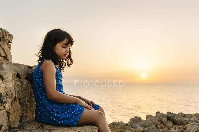 Sad little girl sitting in front of the sea at sunset — Stock Photo