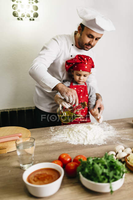 Father and son preparing pizza at home — Stock Photo