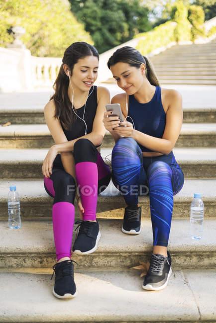 Due giovani donne sportive sedute sulle scale a guardare il cellulare — Foto stock