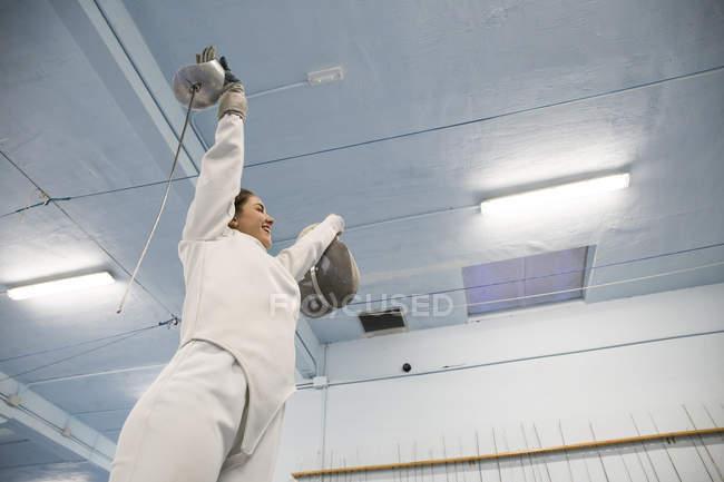 Esgrimista feminina com os braços levantados, celebrando sua vitória após uma luta de esgrima — Fotografia de Stock
