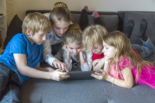 Fünf Kinder gemeinsam auf einer Couch mit digitalem Tablet — Stockfoto