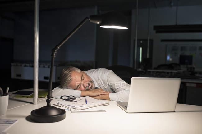 Empresário exausto, dormindo na mesa de escritório com laptop — Fotografia de Stock