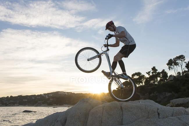 Cyclist jumping on rock on the beach Lloret de Mar at sunset — Stock Photo