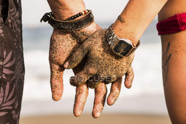 Close-up of couple holding sandy hands — Stock Photo