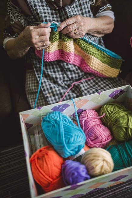 Box of different balls of wool and knitting senior woman — Stock Photo
