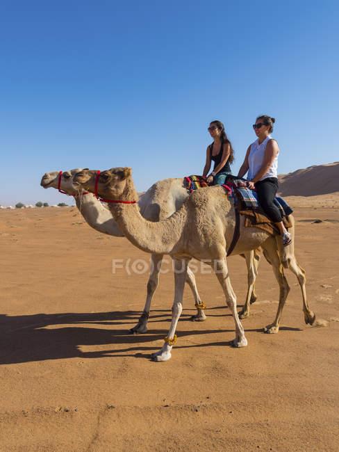 Deserto de Omã, Al Raka, Al Rimal Wahiba, duas mulheres andando em dromedários — Fotografia de Stock
