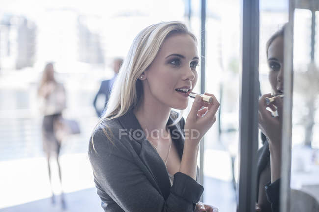 Young businesswoman applying lipstick in window reflection — Stock Photo