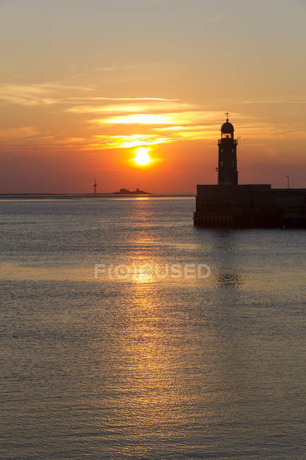 Germany, Bremerhaven, view of lighthouse on hill over water at sunset — Stock Photo