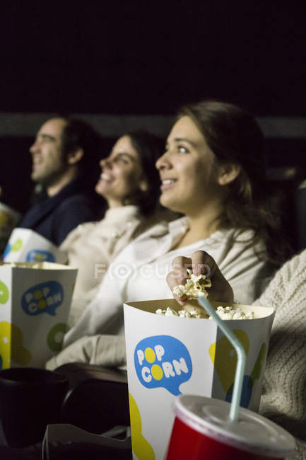Люди смотреть фильм в кино и есть поп-корна — стоковое фото