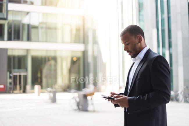 Homme d'affaires utilisant une mini tablette dans un immeuble de bureaux — Photo de stock