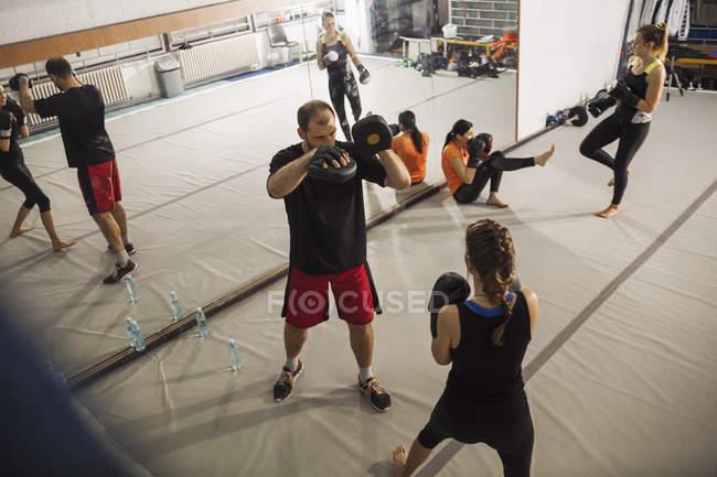 Boxerin sparring mit Trainer in jym — Stockfoto