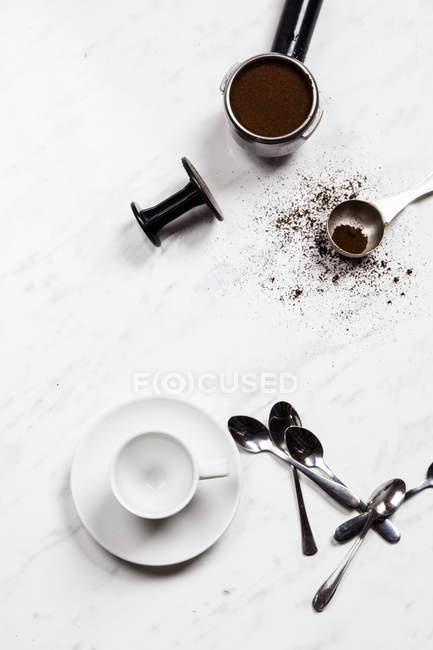 Empty espresso cup, spoons and pressurized portafilter on white marble — Stock Photo