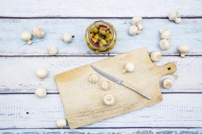 Vaso di champignons sottaceto e champignons bianco fresco su legno bianco — Foto stock