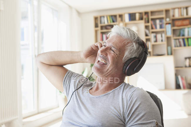 Portrait of relaxed man hearing music with headphones at home — Stock Photo