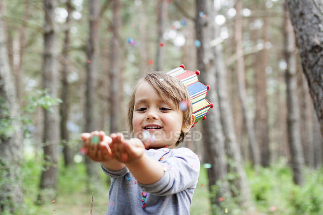 Portrait of smiling little boy wearing paper crown catching confetti — Stock Photo