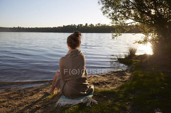 Young woman sitting at a lake at sunset — Stock Photo