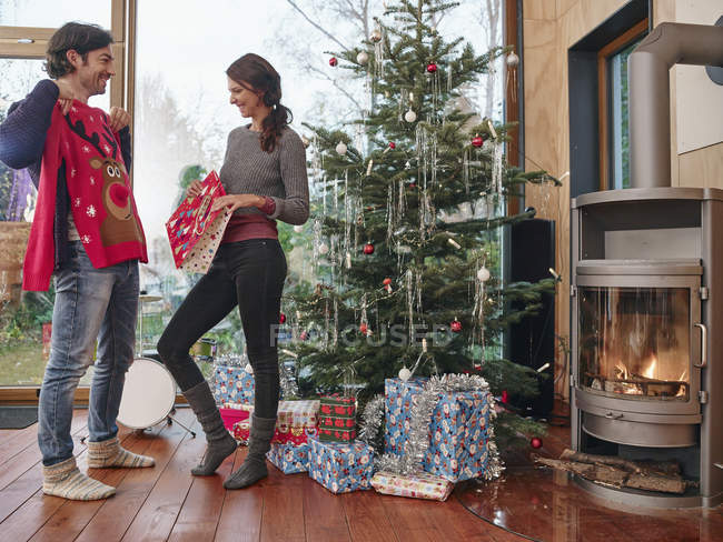 Couple standing in front of Christmas tree unwrapping Christmas jumper — Stock Photo
