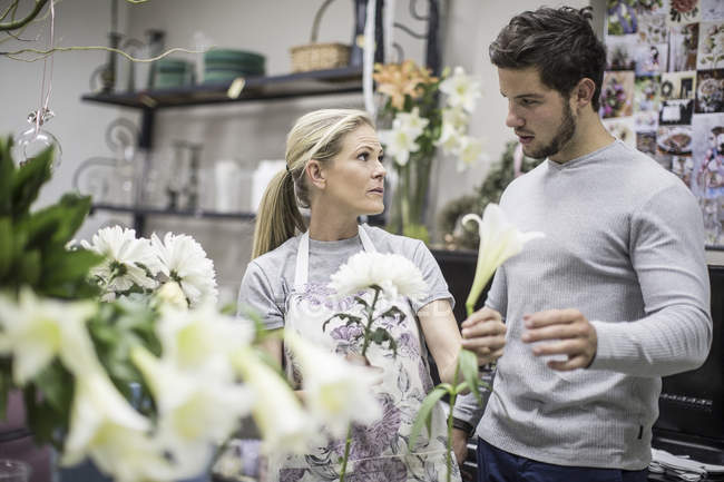 Shop assistant in flower shop advising customer — Stock Photo