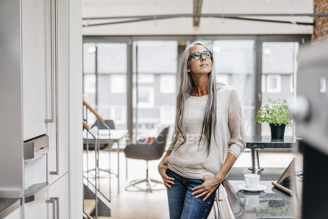Woman with long grey hair standing in modern kitchen and looking up — Stock Photo