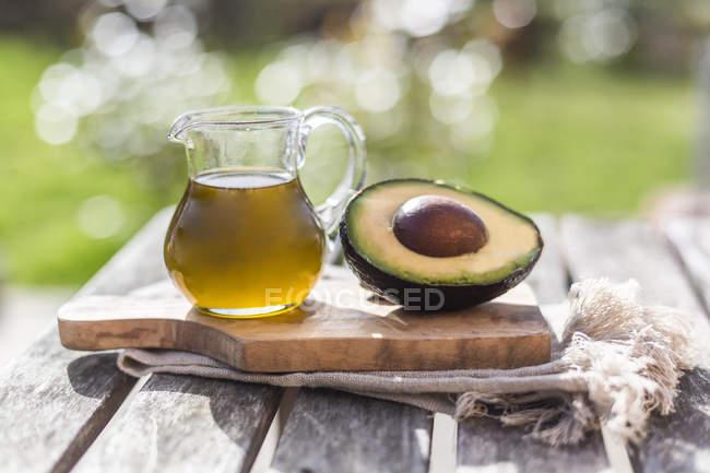 Половина авокадо и стеклянный кувшин масла на деревянной доске — стоковое фото