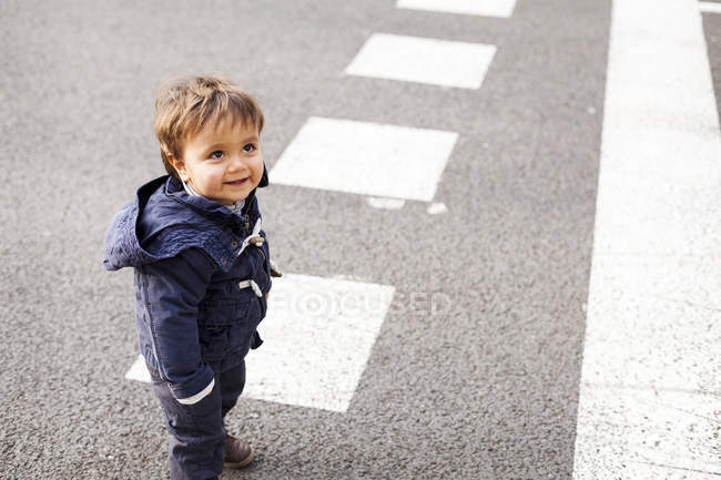 Retrato de um menino sorridente em pé na estrada e olhando para cima — Fotografia de Stock