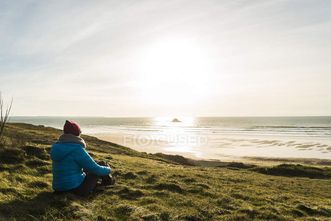 Woman sitting at the coast at sunset, France, Bretagne, Finistere, Crozon peninsula — Stock Photo