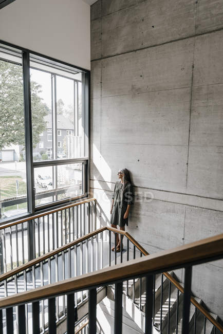 Woman with long grey hair looking out of window on staircase — Stock Photo