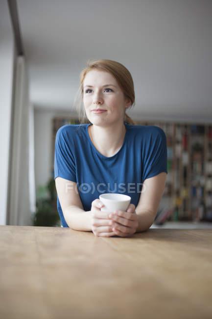 Женщина сидит за столом с чашкой кофе — стоковое фото