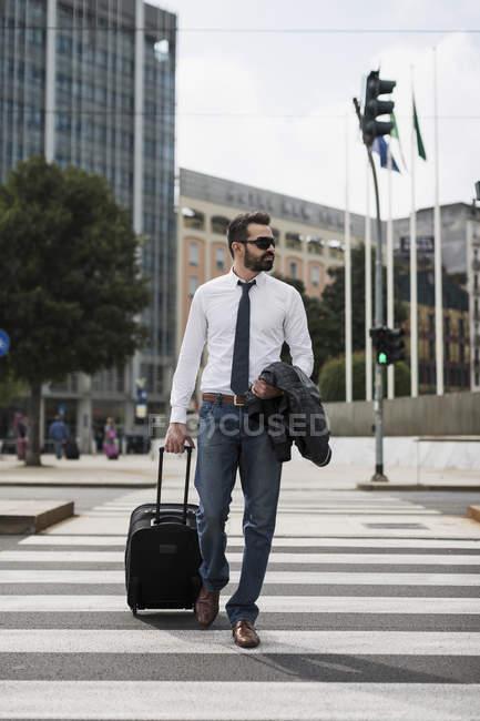 Бизнесмен с чемоданом, пересекающих улицу — стоковое фото