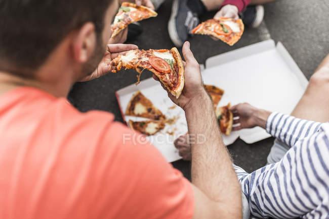 Обрезанный образ молодых людей, которые едят пиццу — стоковое фото