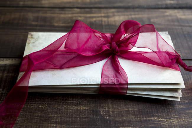 Pila di vecchie lettere d'amore legate con nastro rosso — Foto stock
