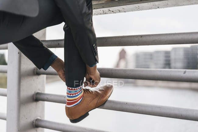 Jeune homme d'affaires liant des lacets sur la balustrade de la rue — Photo de stock