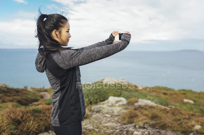 Irlande, Howth, athlète féminine prenant une photo de téléphone portable sur la côte de falaise — Photo de stock
