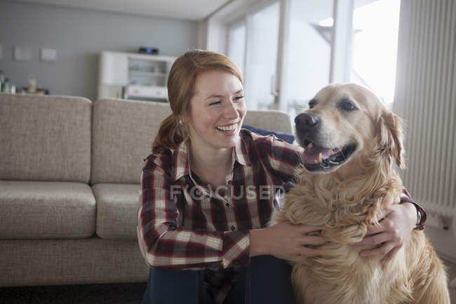Woman hugging dog on floor at home — Stock Photo