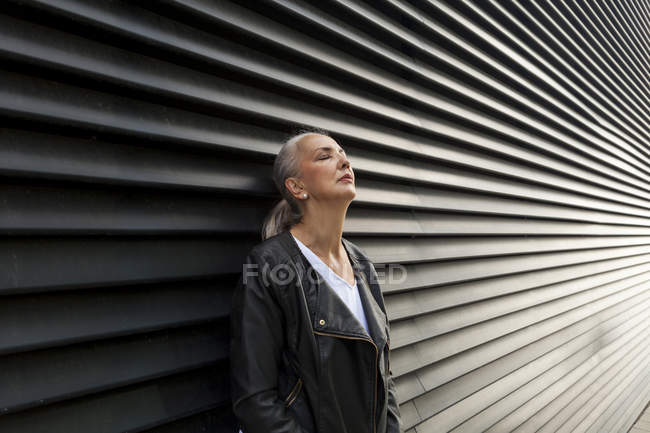 Mature woman with eyes closed leaning against black wall — Stock Photo