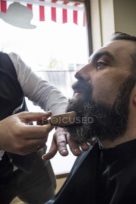 Barber brushing the beard of a man with a hair brush — Stock Photo