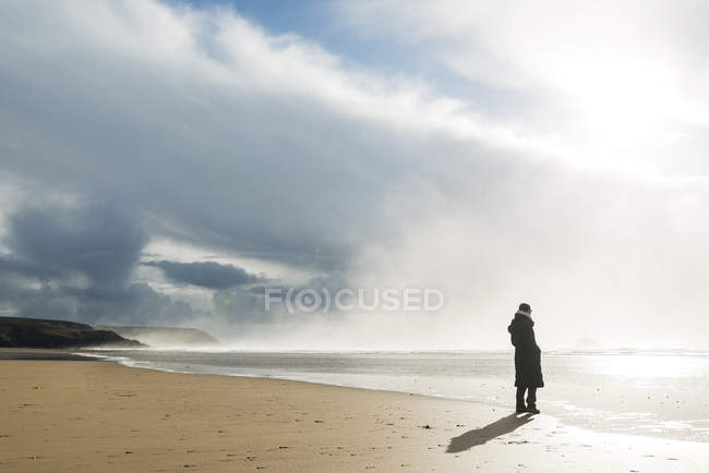 Woman standing on the beach at sunlight, France, Bretagne, Finistere, Crozon peninsula — Stock Photo