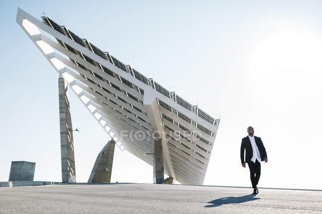 Бізнесмен, ходьба в місто з панелі сонячних батарей на тлі — стокове фото