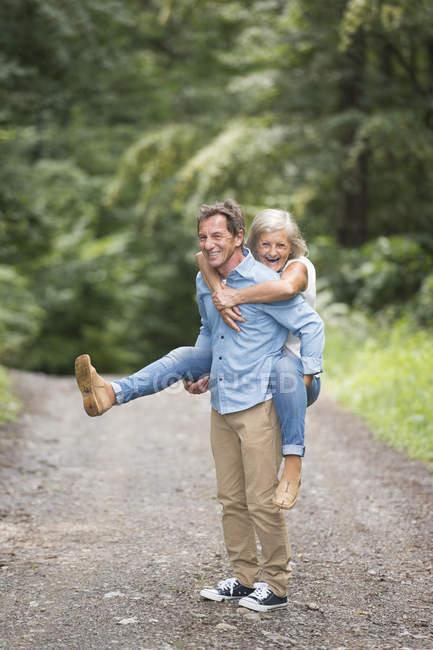 Attivo carino anziano coppia, uomo dando cavalcata a donna nel parco — Foto stock