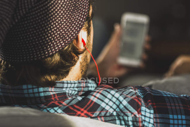 Back view of man hearing music with earphones, close-up — Stock Photo