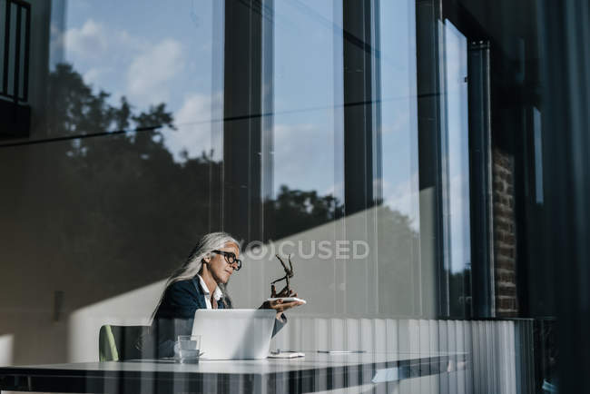 Businesswoman sitting at desk and looking at sculpture — Stock Photo