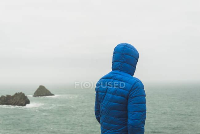 Чоловік, що стоїть на узбережжі з синій жакет з капюшоном — стокове фото