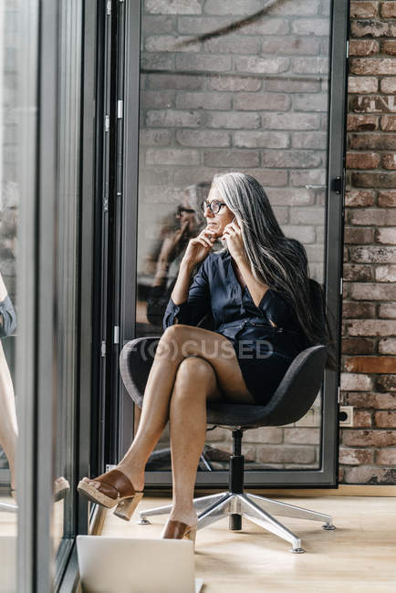 Woman with long grey hair on cell phone sitting at the window — Stock Photo
