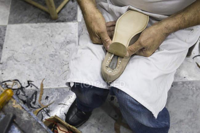 Sapateiro colocando a sola em um sapato em sua oficina — Fotografia de Stock