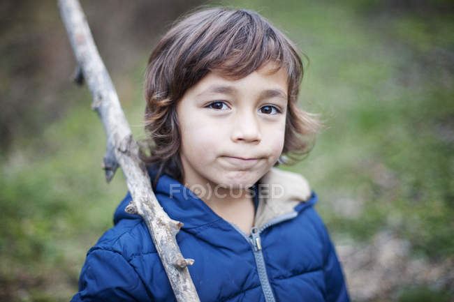 Portrait of little boy with branch in nature — Stock Photo