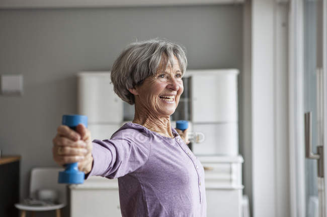 Portrait of happy senior woman doing fitness exercise with dumbbells at home — Stock Photo