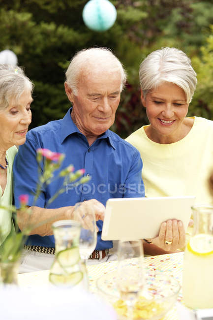Senior man looking at digital tablet with guests — Stock Photo
